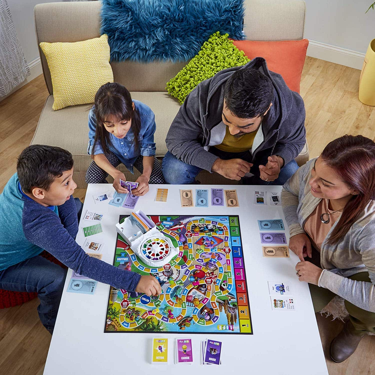 Game of Life 2021 'Your Life Your Way' Total Product Offering with game board, money, cards, and spinner, in a lifestyle photoshoot with family. Made by Hasbro Gaming