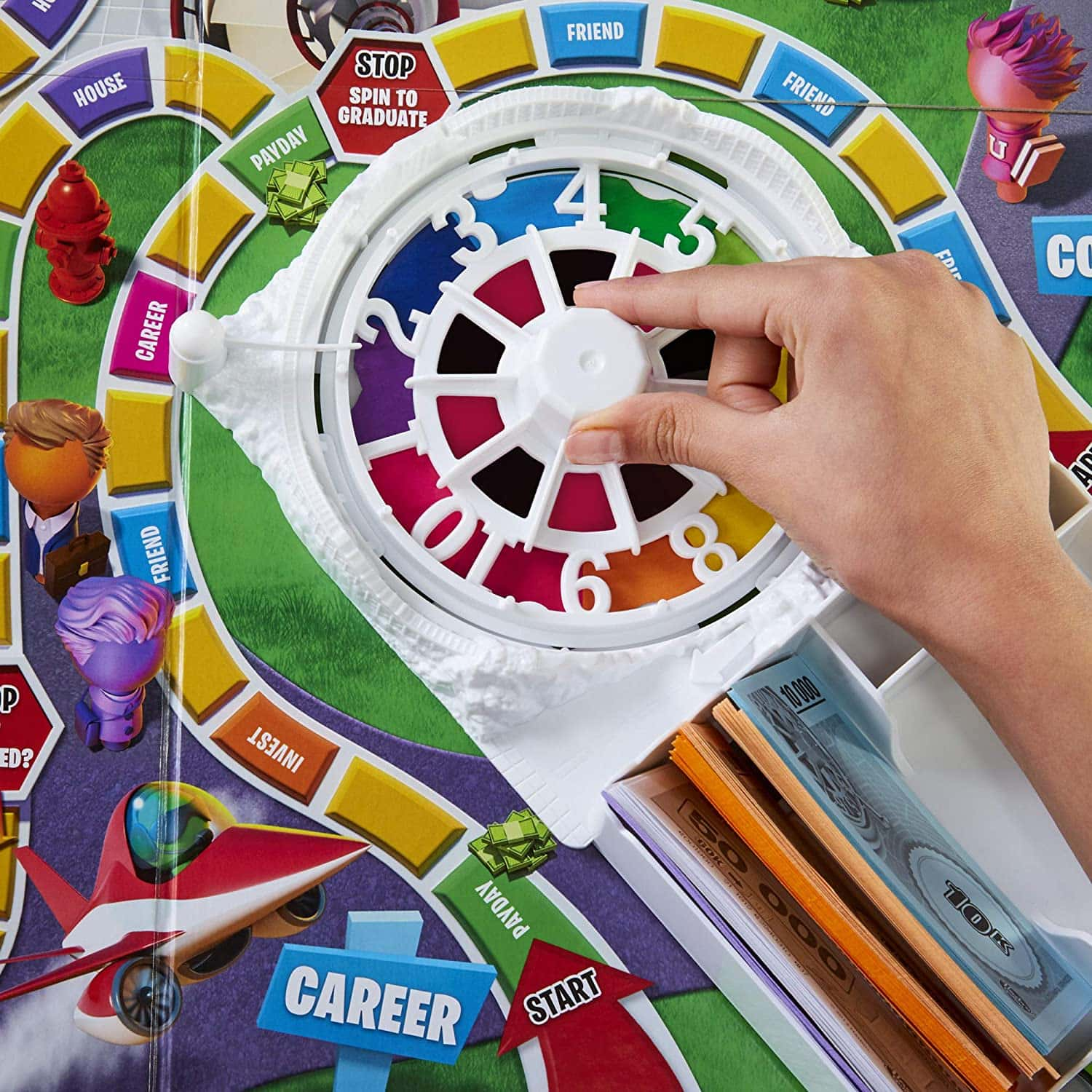 Game of Life 2021 'Your Life Your Way' in a lifestyle photoshoot with a close up the spinner and game board. Made by Hasbro Gaming