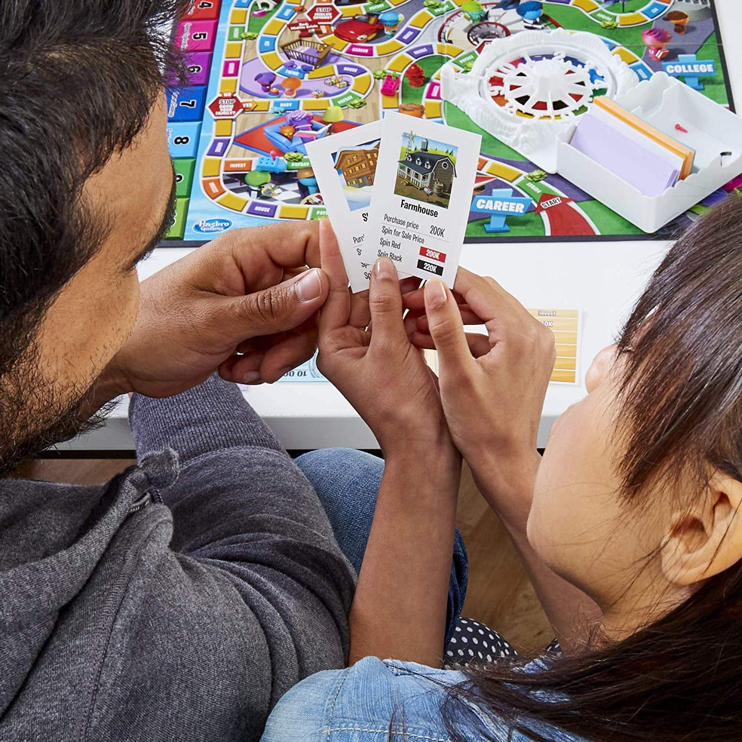 Game of Life 2021 'Your Life Your Way' Total Product Offering with game board, money, cards, and spinner, in a lifestyle photoshoot with 2 people. Made by Hasbro Gaming