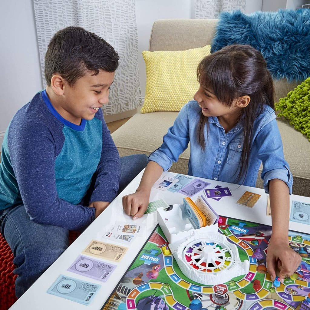 Game of Life 2021 'Your Life Your Way' Total Product Offering with game board, money, cards, and spinner, in a lifestyle photoshoot with 2 kids. Made by Hasbro Gaming