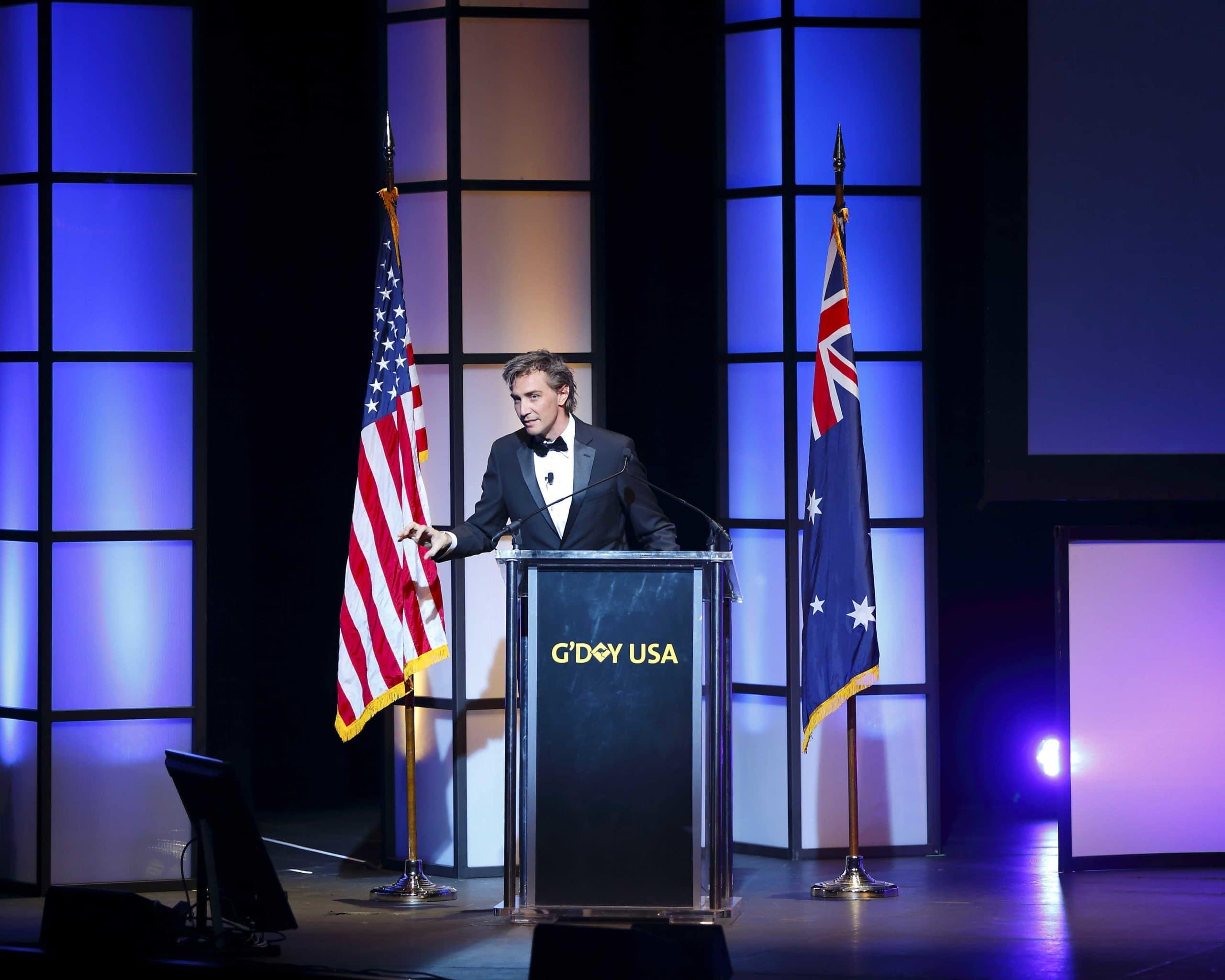 Innovators Xchange 2016 G'Day USA standing at podium hosting the event